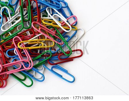 A pile of colored paper clips on white background