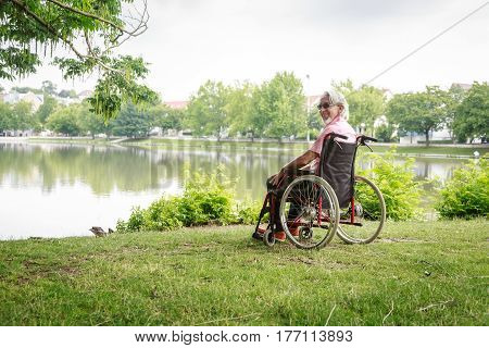 Senior man in wheelchair, enjoying time outdoors.