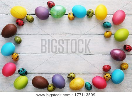 Multicolored eggs with flowers. Easter conceptual background. Top view