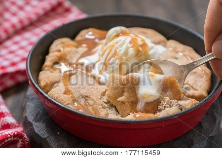 Chocolate chip cookie with ice cream and caramel homemade on a pan.