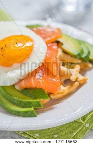 Healthy eating food breakfast oatmeal waffles, smoked salmon, avocado and fried egg