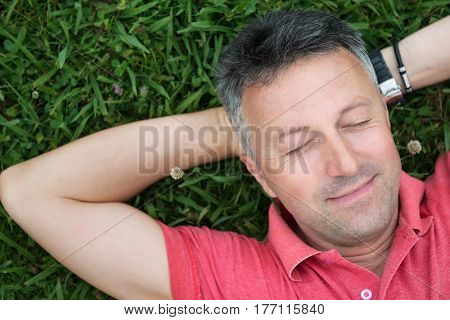 Portrait of handsome mid-adult man posing on summer meadow in green grass.