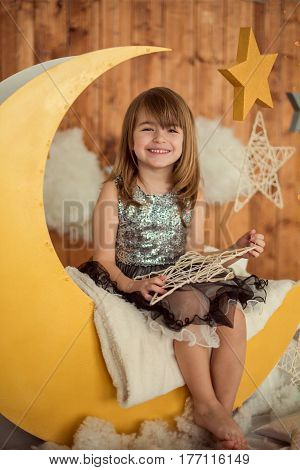 Happy baby girl 5-6 year old sitting on a wooden month with a decorative star in her hands. Children's photozone. Childhood.