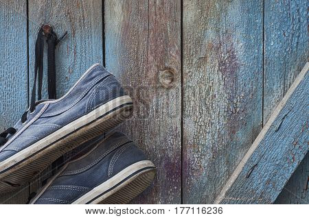 pair of old dirty and worn blue sneakers hang on a nail on a wooden cracked wall