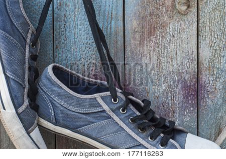 pair of old worn blue shoe hanging on a nail on a wooden cracked wall