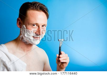 a man is preparing for his morning shave, showing us his razor