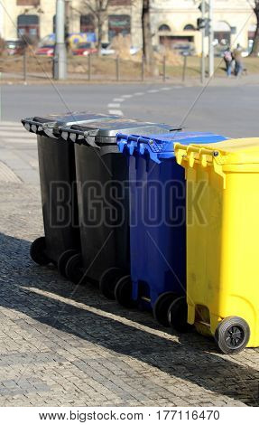four cloured dust bins on the street