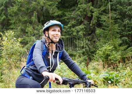 Young smiling woman Young woman riding bicycle in mountain forest on summer day