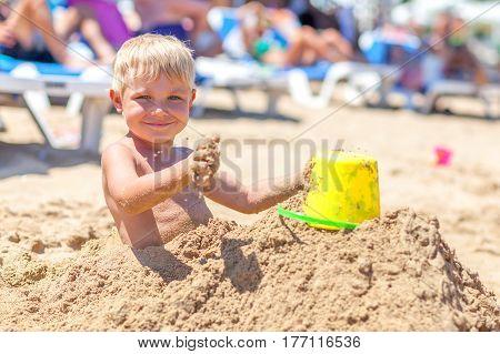Cute boy buried in sand on the sea beach