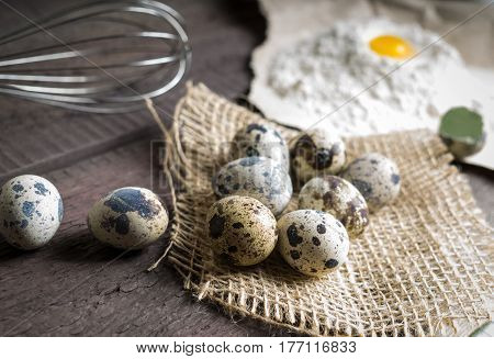 Quail eggs flour whisk on wooden background. Shallow deep of field blurred macro shot
