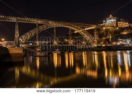 Night view of Porto with Dom Luis I Bridge, Duoro river and Mosteiro da Serra do Pilar with reflection in water