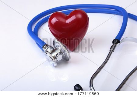 Medical stethoscope and red heart isolated on white.
