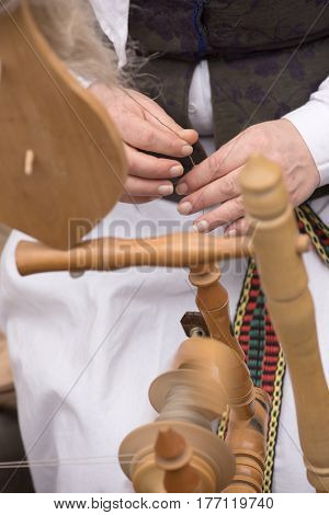 Hands of woman in action spinning wool into yarn with a spinning wheel