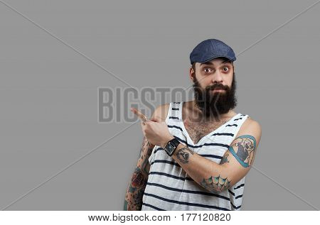 Surprised bearded man point to the right andd look to the camera. Guy show dangerous and take attention. Shoked emotion of high prices. Big sales season.