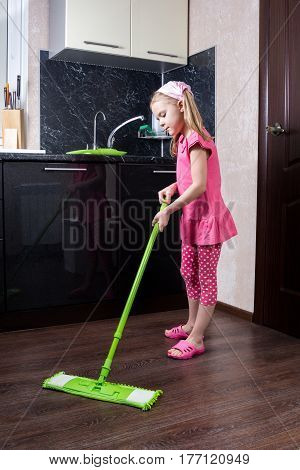 Little Girl Washes Floor With A Mop