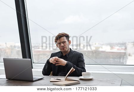 Bussiness man with stylish look in his office with window wall background sitting and look to the camera. Chief meet job seeker for interview.