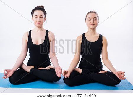 Young man and woman doing yoga and meditating in lotus position isolated on white background