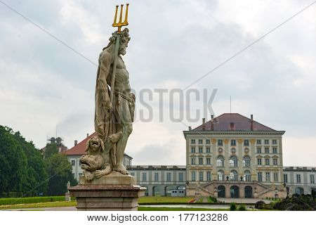Munich, Germany - June 8. 2016: Statue Pluto by Dominik Auliczek. And the rear view of the Nymphenburg Palace. Munich, Bavaria, Germany