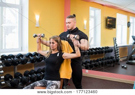 Woman with her personal fitness trainer in the gym exercising power gymnastics with a barbell.