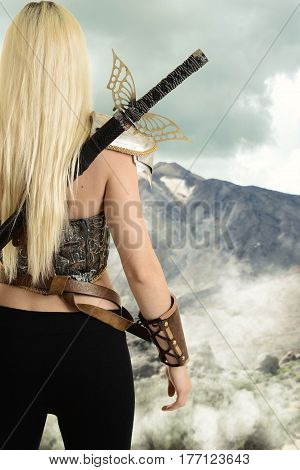 back of female warrior looking at mountain