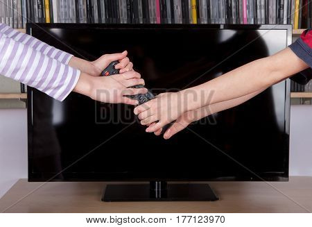 Children's hands fighting for the remote control in front of the tv.