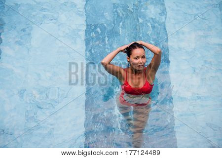 Top view of a beautiful sexy adult asian woman in the swimming pool.