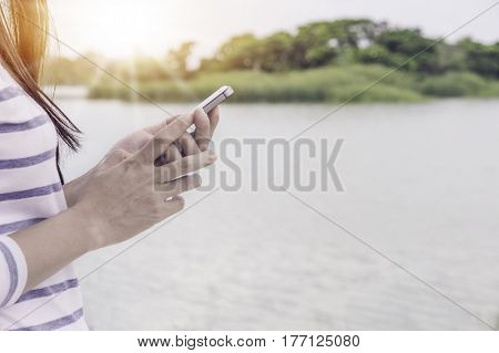 Closeup of hand holding using smartphone with blur lake nature background.