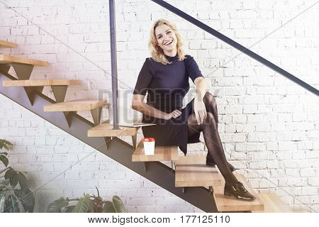 Happy smiling businesswoman sitting on stairs in modern office working at laptop and having coffee sunshune daylight. Business concept people job marketing sale