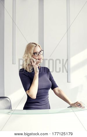 Beautiful blonde friendly woman behind the reception desk meet and smiling. Sunshine in modern office. Business conception working people. Portrait Vertical