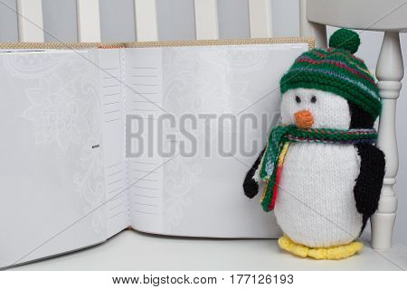 Stuffed penguin toy on white rocking chair with photo album