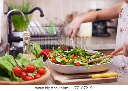 Little girl mixing the chopped vegetables into a salad - working with two wooden spoons, closeup on hands, shallow depth