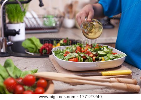 Child hand pouring oil on a fresh mixed vegetables salad plate - closeup on hand and salad in a kitchen setting, shallow depth