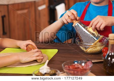 Kids preparing a pizza together - closeup on hands stretching dough and grating cheese, shallow depth