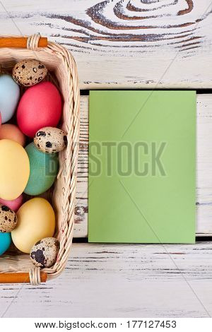 Empty card and easter basket. Paper on white wood background. Send Easter greetings.