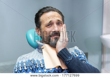 Mature man in dental chair. Adult male having toothache. Get rid of tooth pain.