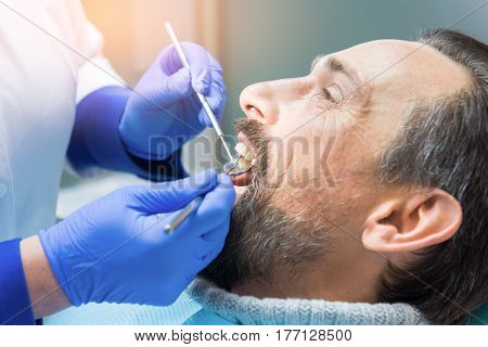 Hands of dentist with tools. Patient at the stomatologist.