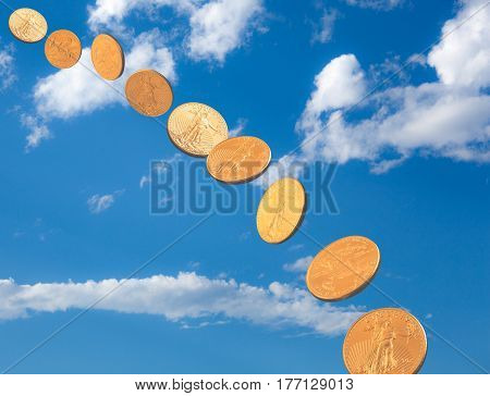 Stream of US gold treasury coins falling out of a blue sky to earth to suggest wealth or falling prices for gold