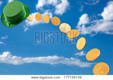 Stream of US gold treasury coins falling out of a blue sky to earth with green irish style hat for St Patricks day