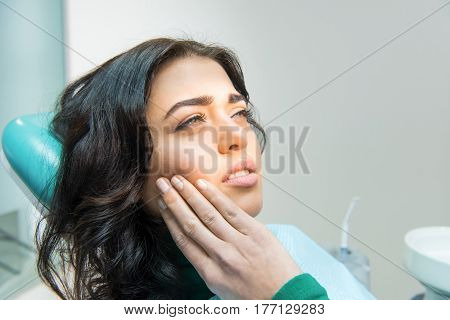 Young female having toothache. Upset woman at the dentist. Constant pulsating pain.