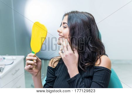Female checking teeth in mirror. Smiling woman at dentist office. Smile wider and be beautiful.