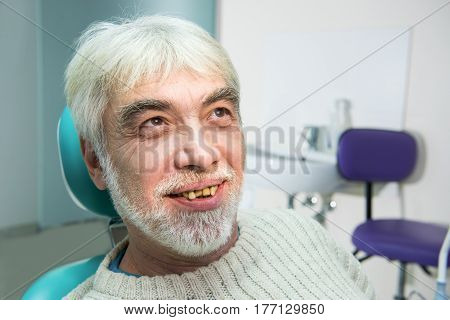 Old man with yellow teeth. Senior patient of stomatologist. Cure dental diseases.