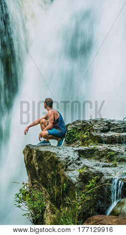 Man sitting in Front of Tegenungan Waterfall near Ubud in Bali, Indonesia.
