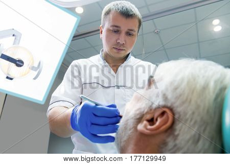 Male dentist working. Stomatologist looking at patient. International dental clinic.
