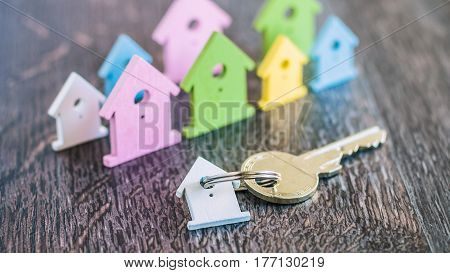 Silver Key with Breloque in front of Miniature Symbols of Houses in Different Colours on Dark Wooden Surface.
