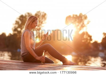 Alone lady sitting on dock near water with bottle and cellphone at sunset