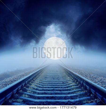 full moon over railroad in dark clouds