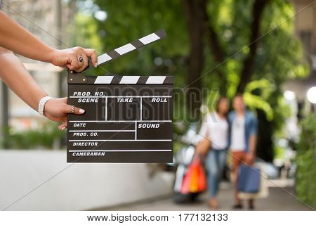 Female  holding clapper board with shopping couple in background, concept start sale