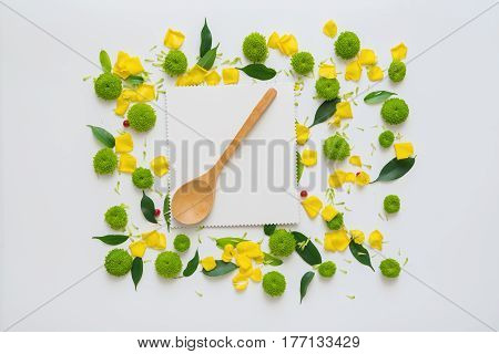 Sheet of paper and wooden spoon with pattern from petals of chrysanthemum flowers, ficus leaves and ripe rowan on white background. Overhead view. Flat lay.