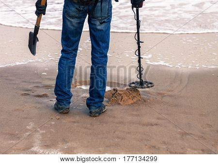 man using a metal detector to search for metal or lost treasure on the sandy beach. He has showel in hand