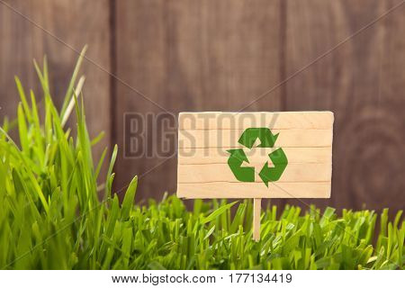 Signboard recycling on Grass background of wood planks, Fresh green lawn near rustic grunge fence